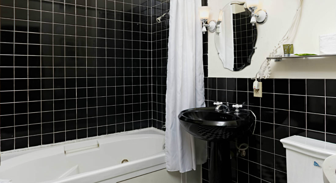 In this black and white bathroom a mirror hangs above the sink next to the shower