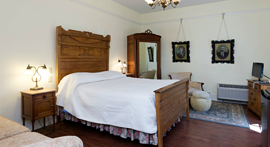 In a white guestroom a well-made white bed rests between a brown wardrobe and nightstand