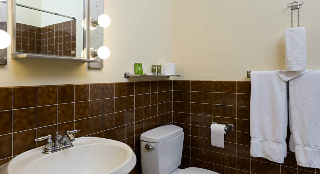 In a cream and brown bathroom a mirror hangs above the sink next to the white toilet