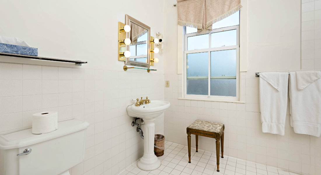 light comes through the window in this white bathroom with a sink and toilet and small seat