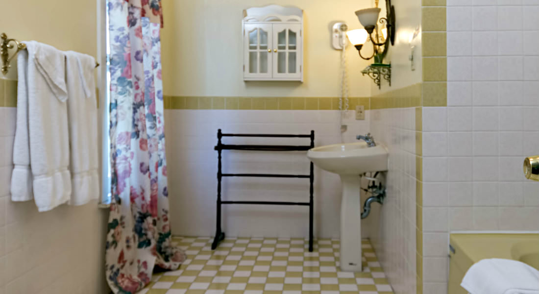 A black towel rack rests next to the white sink in this yellow and white bathroom