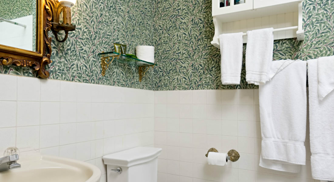 white towels hang from a rack on the wall in this green and white bathroom