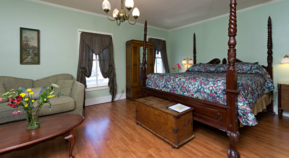 A beautiful four-post bed with a floral bedspread rests across from a couch in this green guestroom