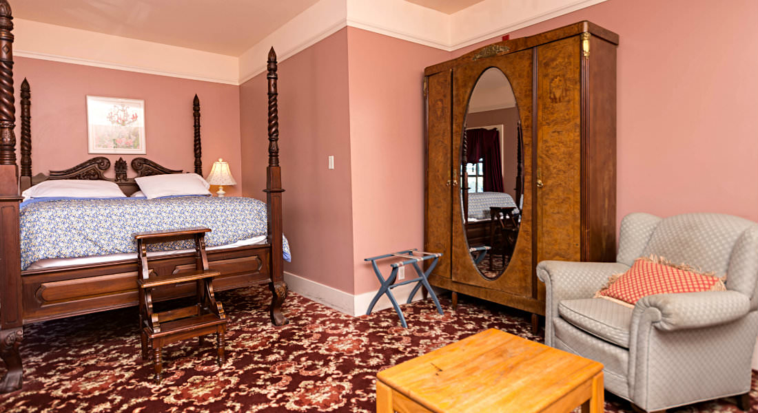 A beautiful four-post bed rests across from a brown mirrored wardrobe of this pink guestroom