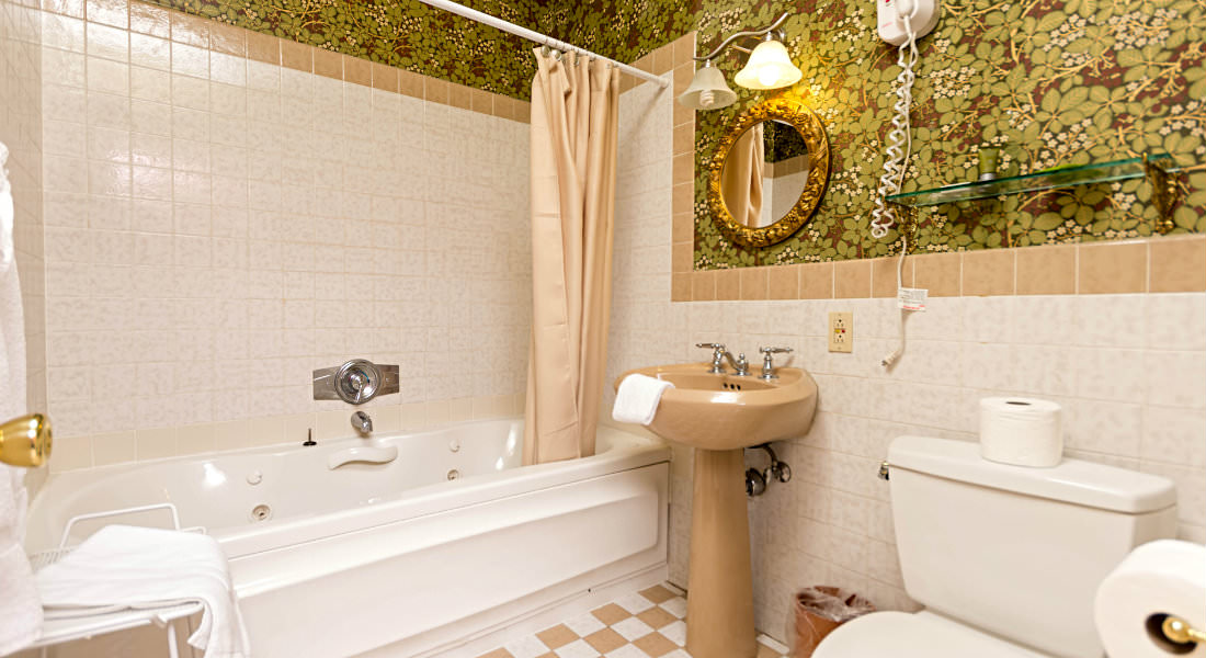 Green and gold accent this unique bathroom with a gold sink between the toilet and tub