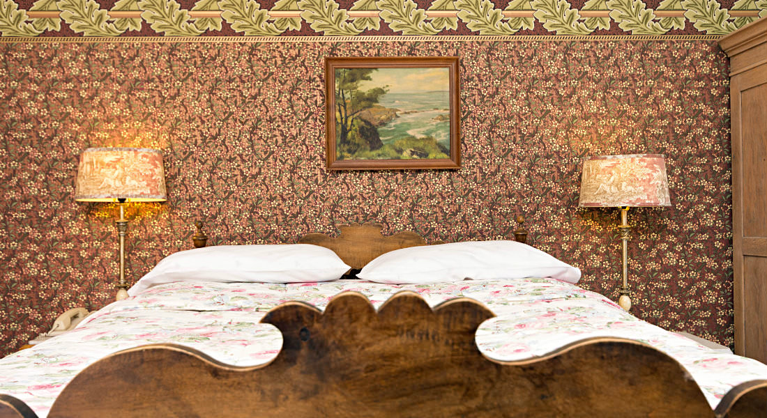 Two lamps sit along side this floral print bed, an old pictures hangs above the bed