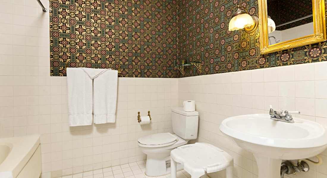 white towels hang on the wall in this bathroom with green and gold wallpaper